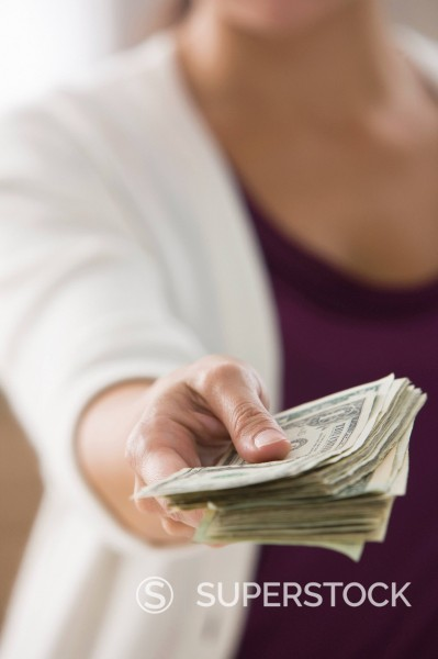 Mixed race woman holding out dollar bills : Stock Photo