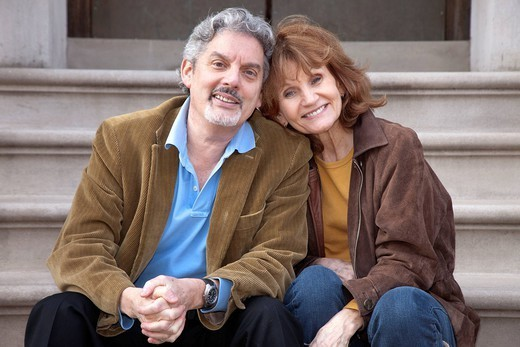 Caucasian couple sitting on front stoop : Stock Photo