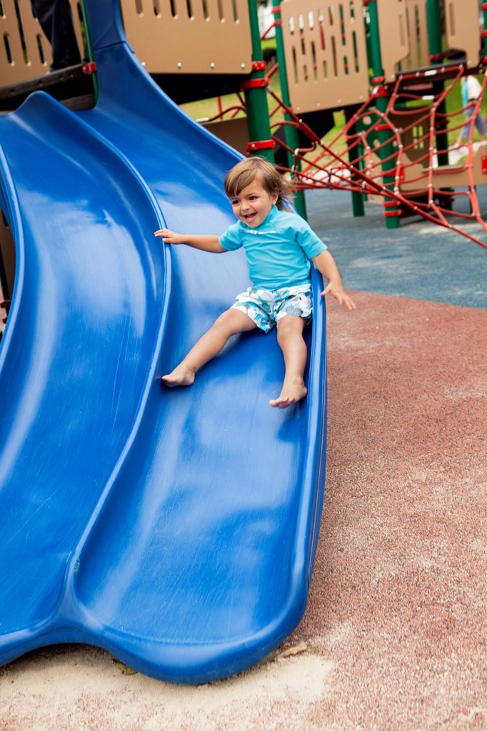 Mixed race boy sliding down slide in playground : Stock Photo