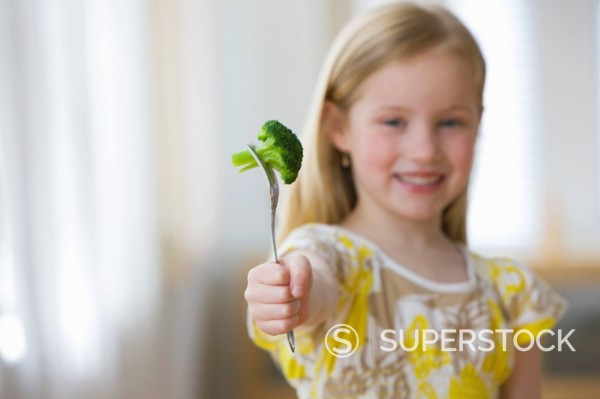 Smiling girl holding broccoli on fork : Stock Photo