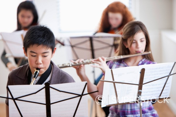 Students playing instruments in music class : Stock Photo