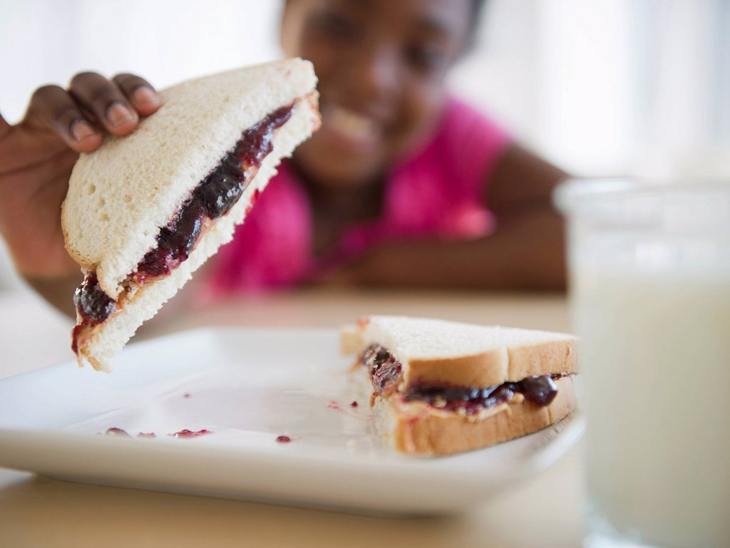 Black girl eating peanut butter and jelly sandwich : Stock Photo