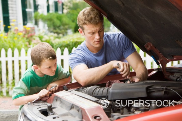 Stock Photo: 1589R-159294 Caucasian boy watching father work on car engine