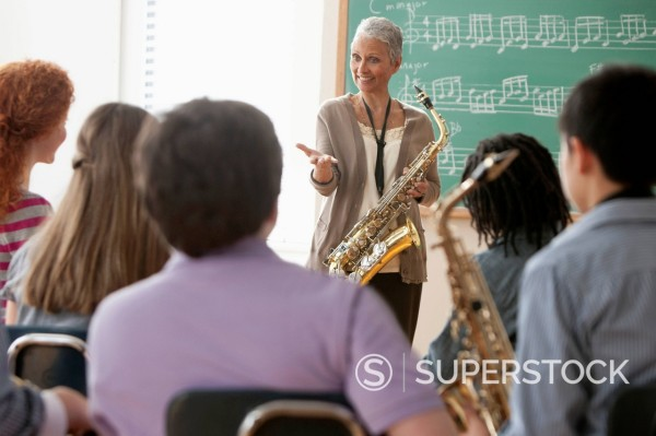 Students listening to teacher in music class : Stock Photo