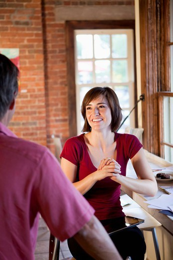 Hispanic woman greeting friend in cafe : Stock Photo