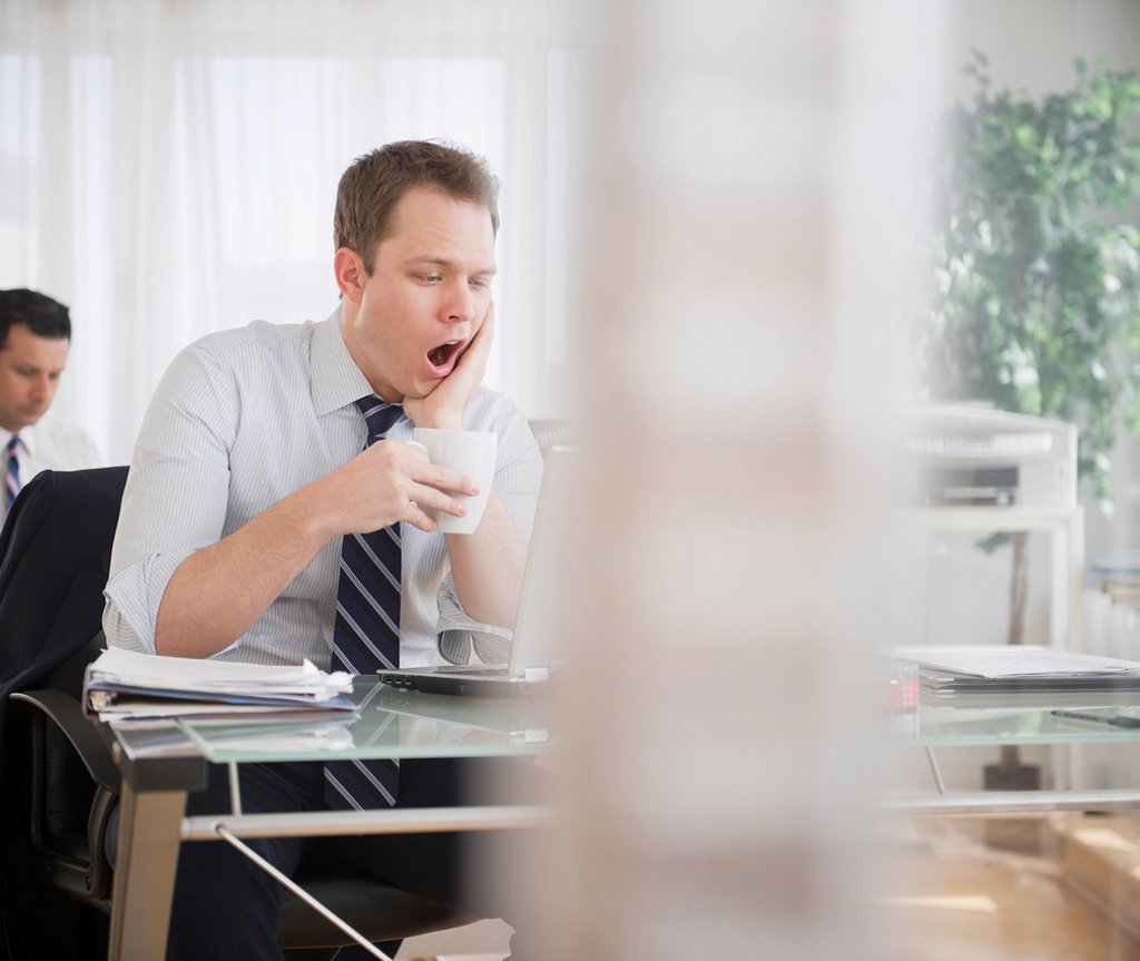Caucasian businessman drinking coffee and yawning : Stock Photo
