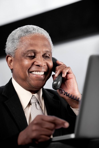 Black businessman talking on telephone and using laptop : Stock Photo