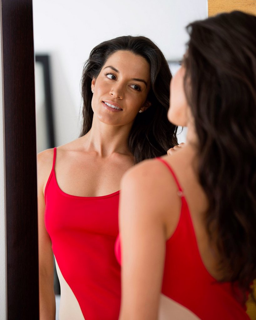 Hispanic woman looking at her reflection : Stock Photo