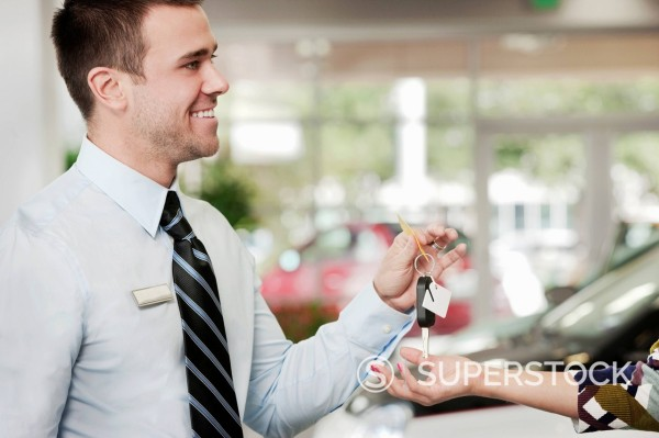 Man handing woman keys to new car in showroom : Stock Photo