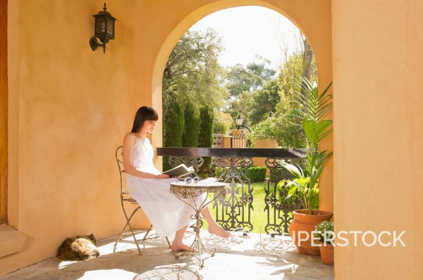 Pacific Islander woman reading book on patio : Stock Photo