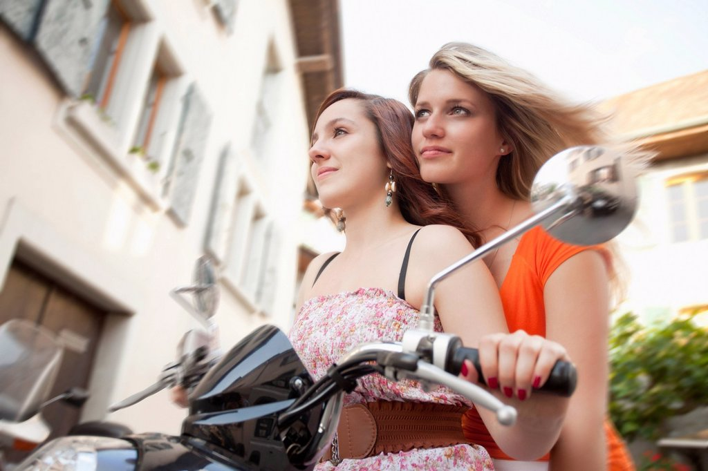 Caucasian friends riding scooter together : Stock Photo