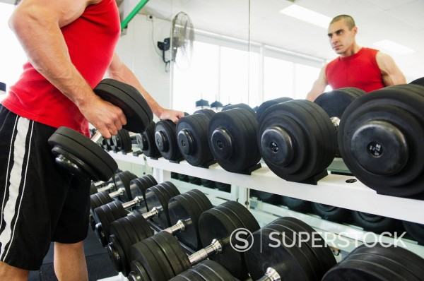 Middle Eastern man exercising with dumbbells : Stock Photo