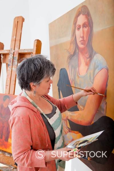 Caucasian artist painting in art studio : Stock Photo