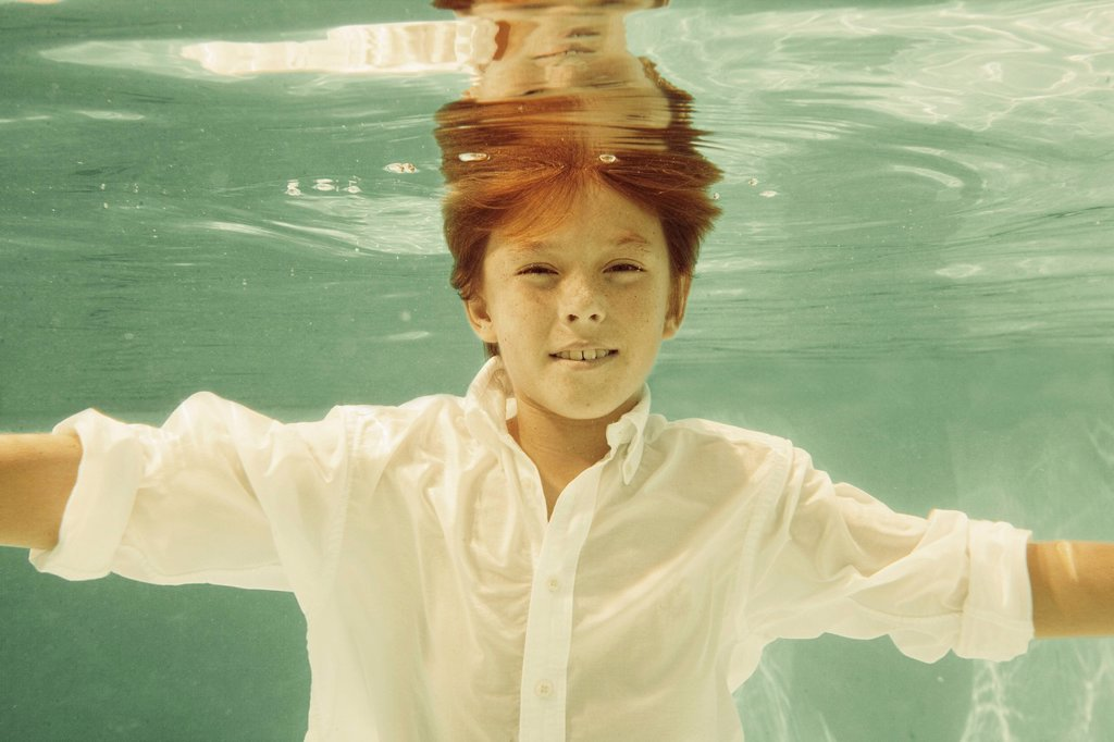 Stock Photo: 1589R-160155 Boy in shirt swimming underwater in swimming pool