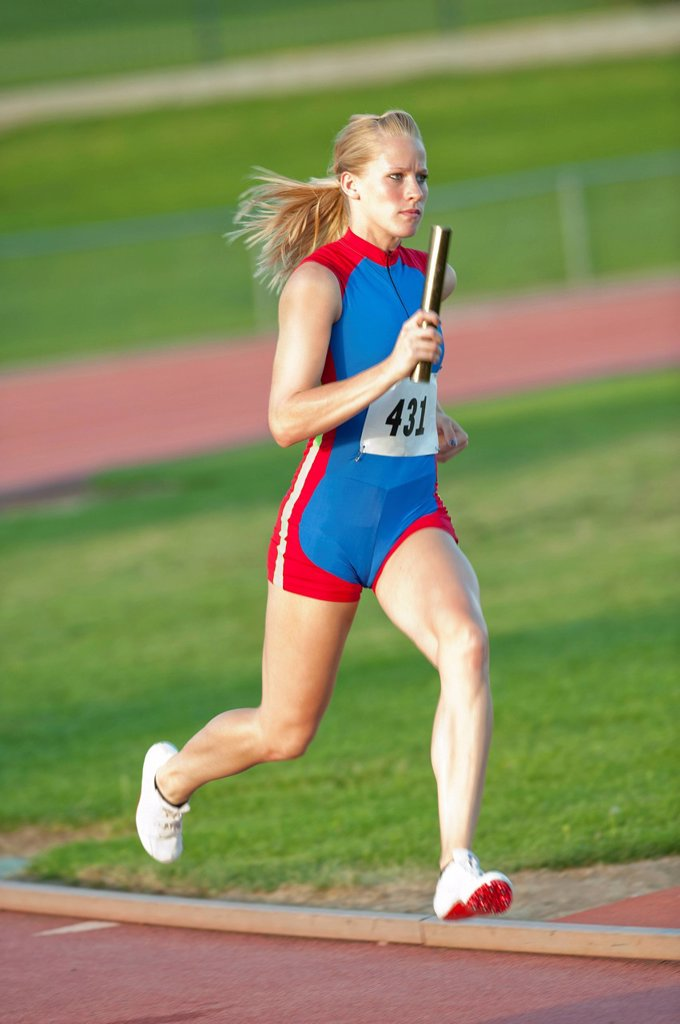 Stock Photo: 1589R-160352 Caucasian runner holding baton running on track