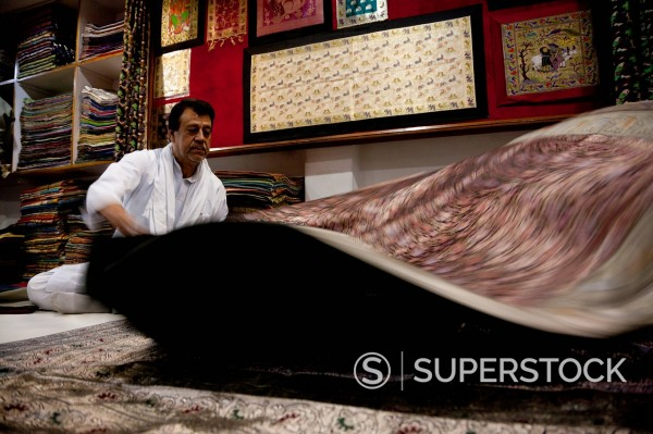 Indian man shaking carpet : Stock Photo