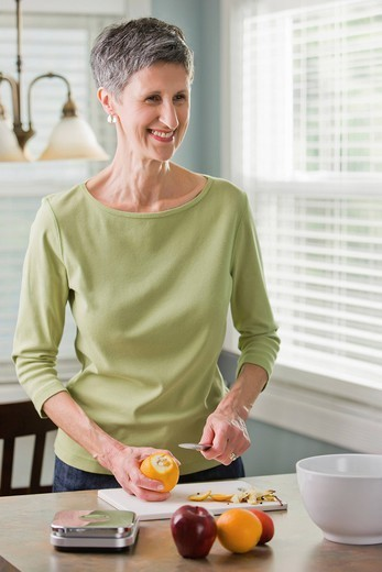 Senior woman cutting fruit : Stock Photo
