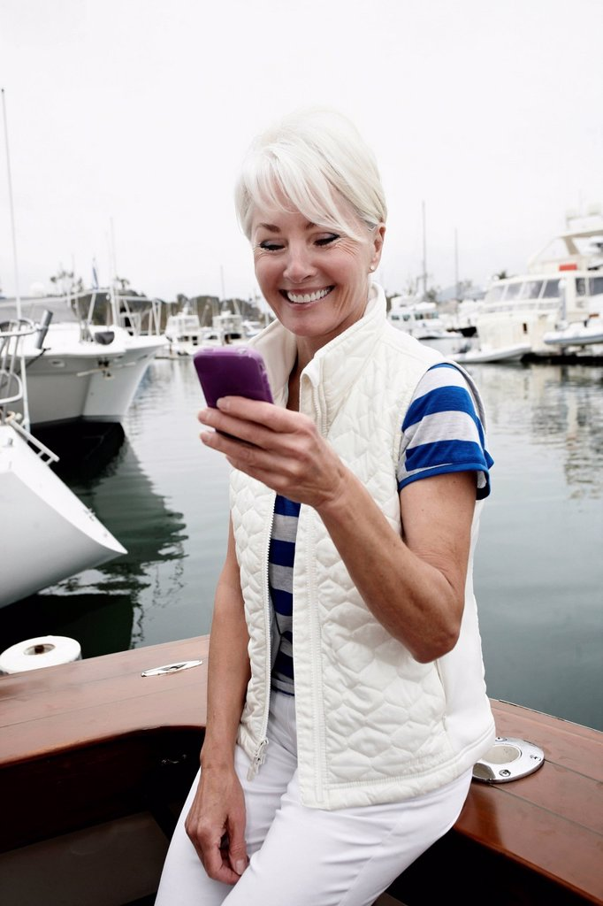 Stock Photo: 1589R-160478 Woman using cell phone in marina