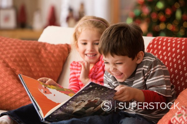 Children reading Christmas book together : Stock Photo