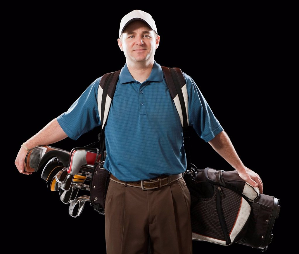 Stock Photo: 1589R-160533 Caucasian golfer carrying golf bag