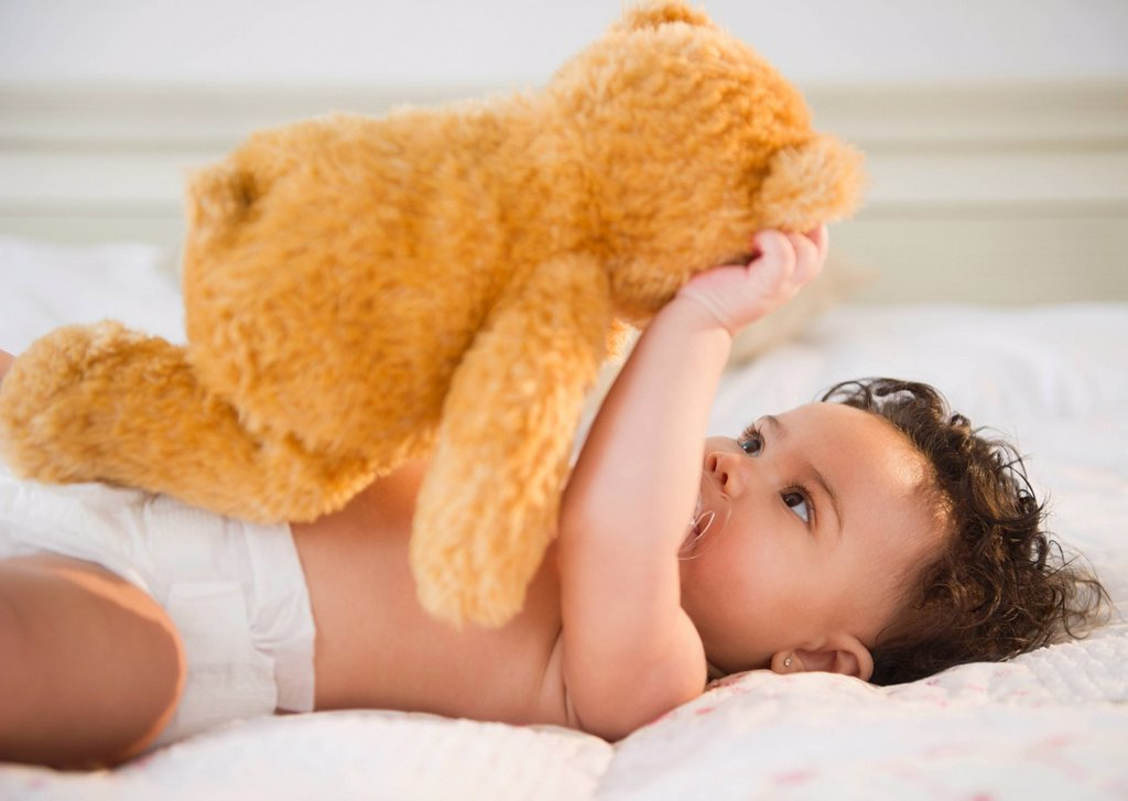 Stock Photo: 1589R-160548 Mixed race baby holding teddy bear