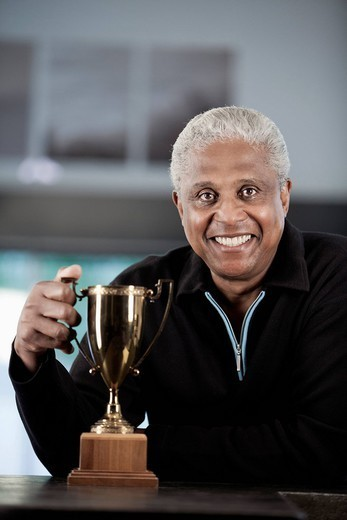 Proud Black man holding trophy : Stock Photo