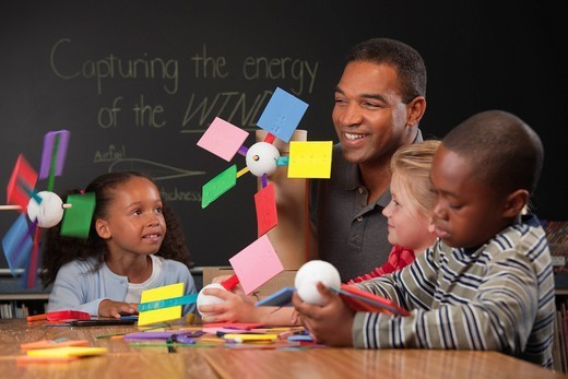 Stock Photo: 1589R-160601 Teacher and children making paper wind turbines in classroom