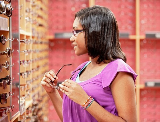African American girl trying on eyeglasses in store : Stock Photo