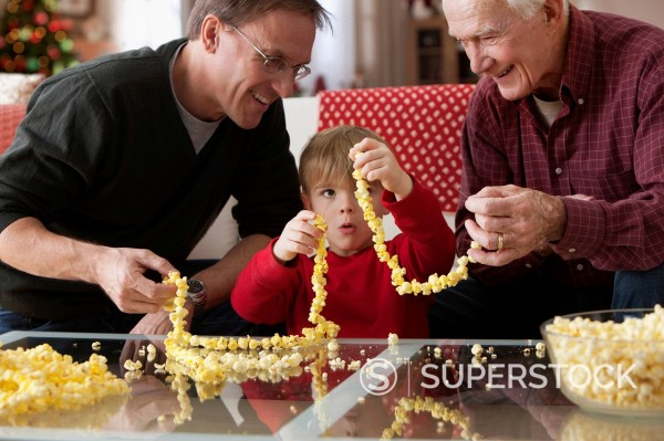 Stock Photo: 1589R-160632 Caucasian father, son and grandson stringing popcorn