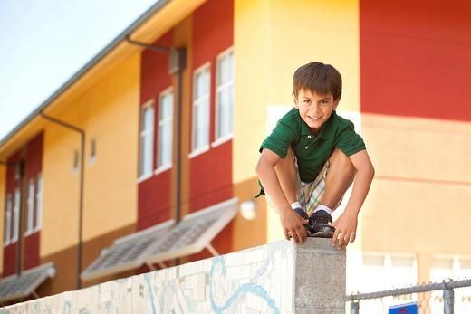 Mixed race boy squatting on wall : Stock Photo