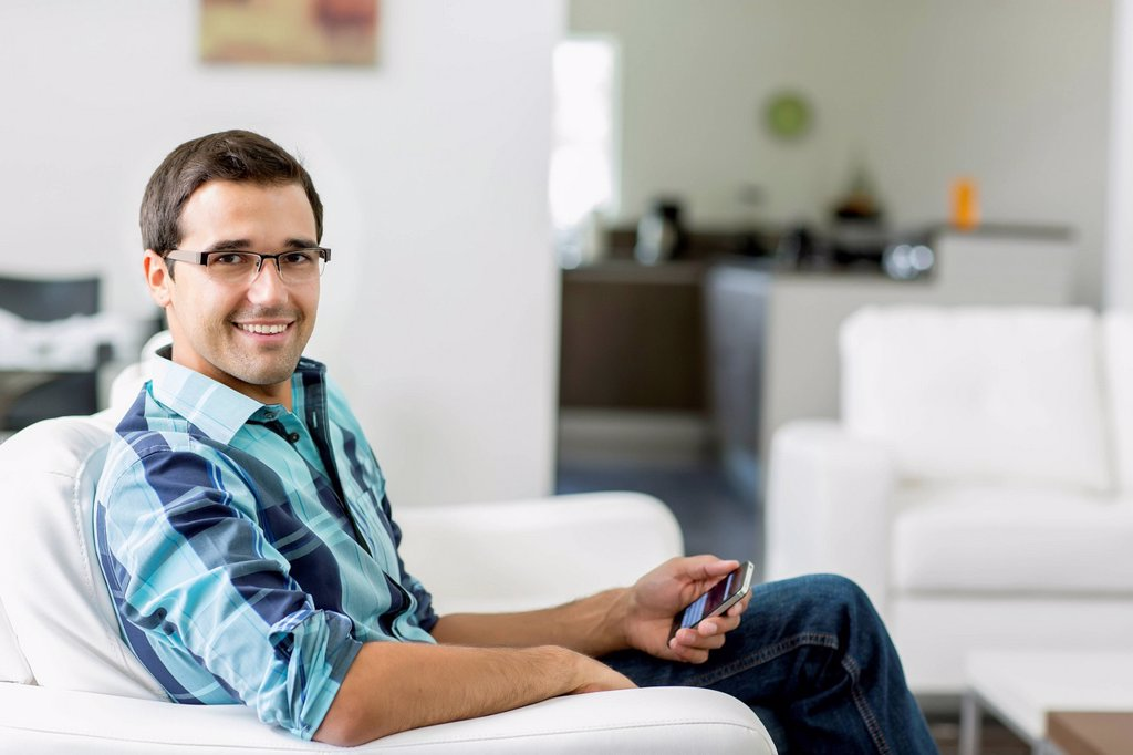 Mixed race man sitting on sofa holding cell phone : Stock Photo
