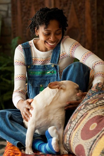 Black woman petting her dog : Stock Photo