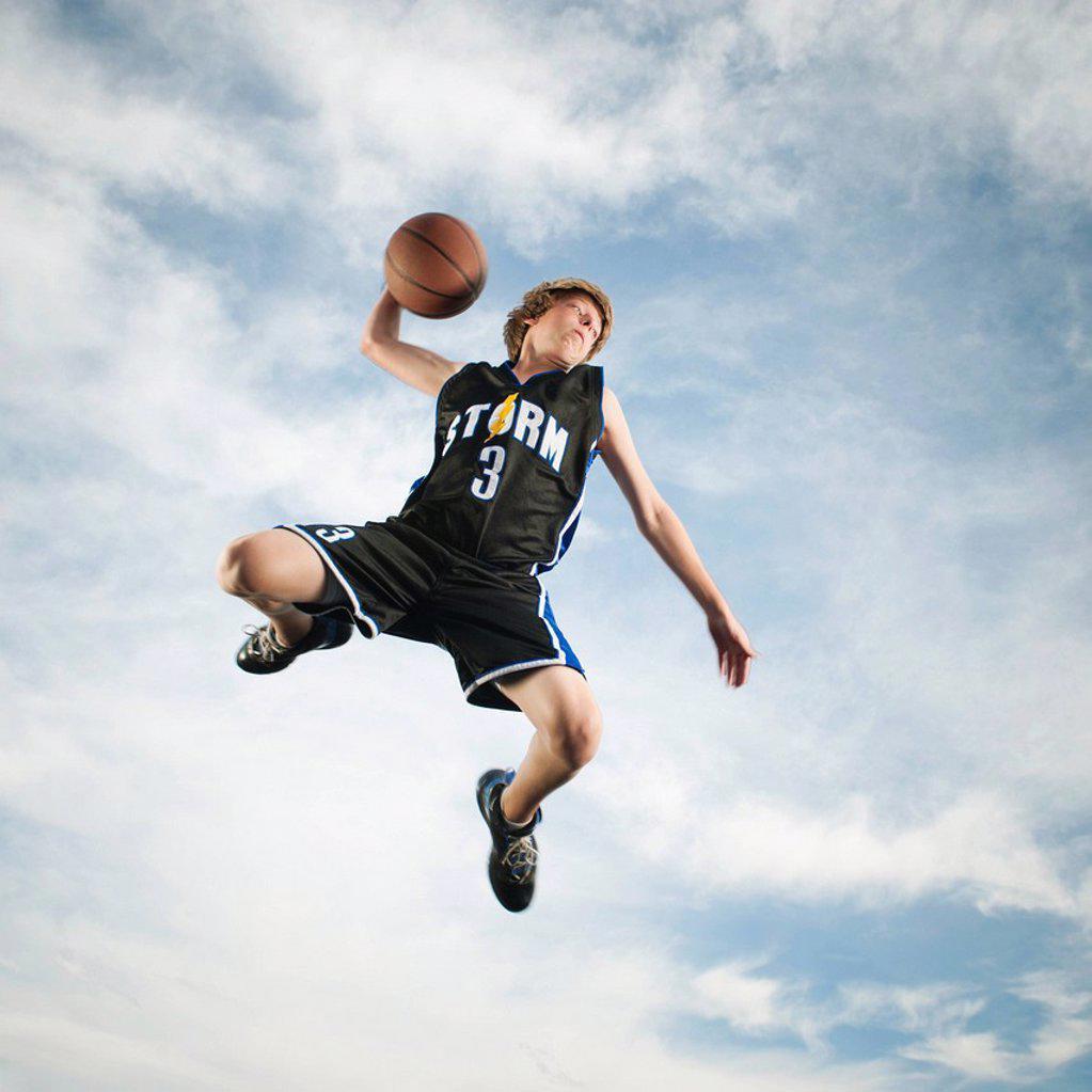Caucasian teenager playing basketball : Stock Photo