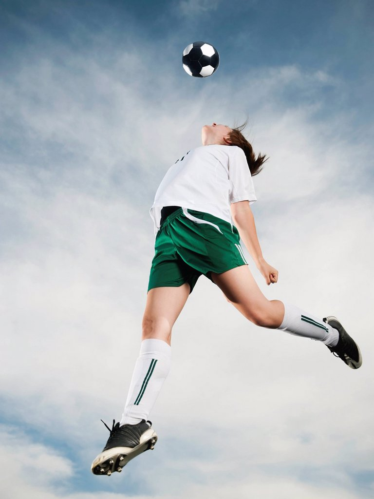 Caucasian teenager heading soccer ball in mid_air : Stock Photo