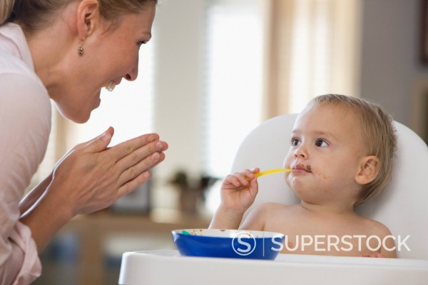 Caucasian mother clapping for baby daughter feeding herself : Stock Photo