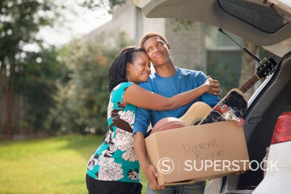 Stock Photo: 1589R-162765 Mother hugging teenage son as he packs for college