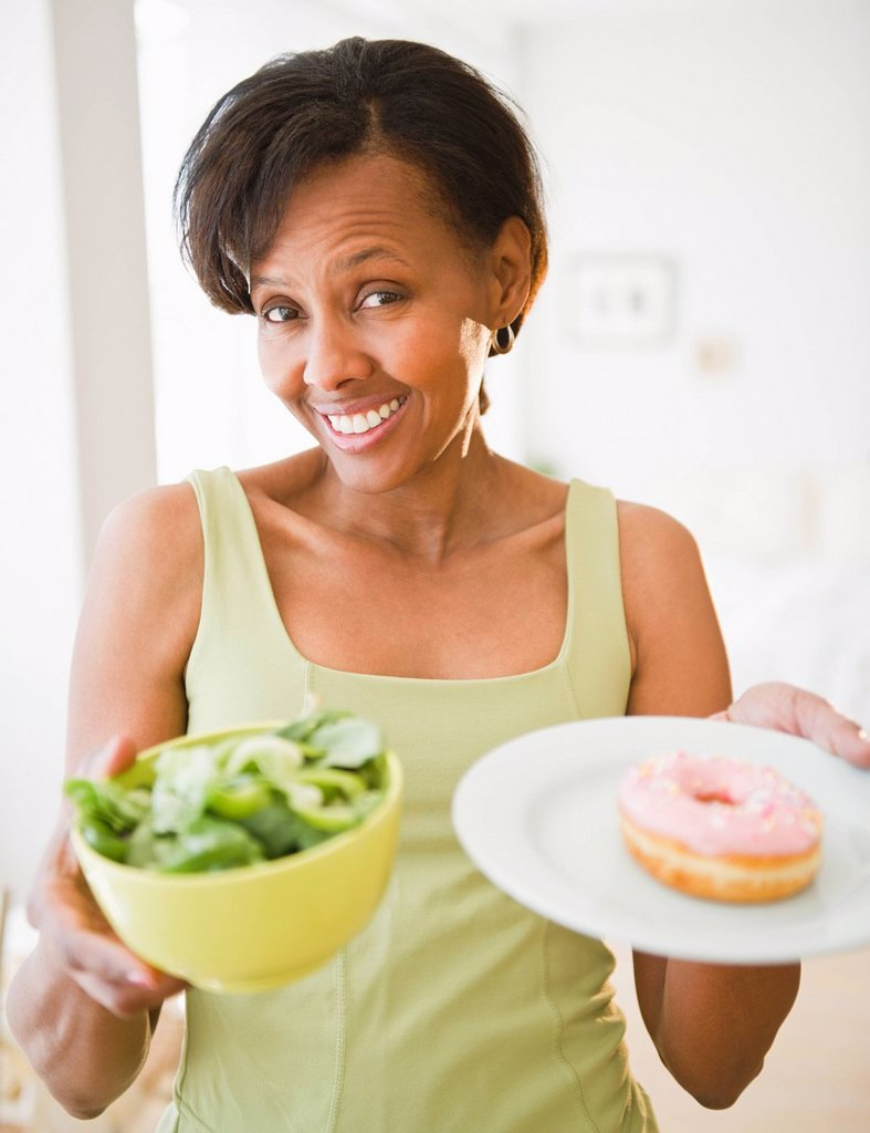 Stock Photo: 1589R-162849 Black woman holding salad and donut