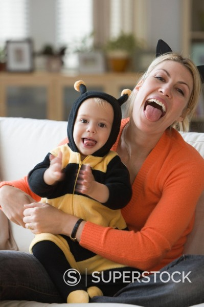 Caucasian mother sitting with baby daughter in bee costume : Stock Photo