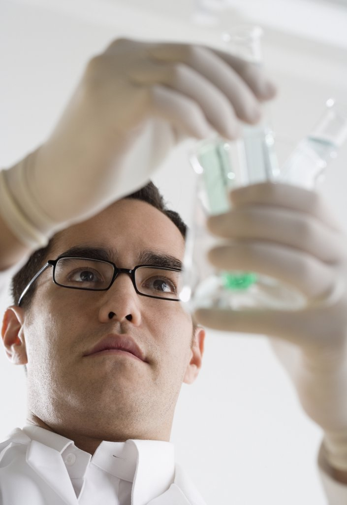 Stock Photo: 1589R-16312 Scientist examining chemicals in test tubes