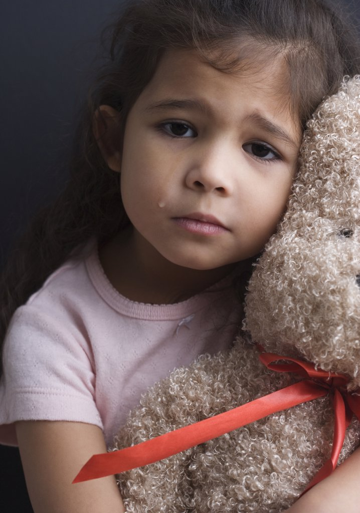 Portrait of girl crying and hugging teddy bear : Stock Photo