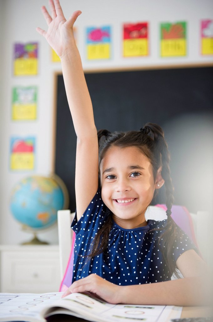Mixed race girl raising her hand in classroom : Stock Photo