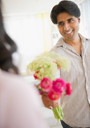 Mixed race man giving girlfriend flowers : Stock Photo