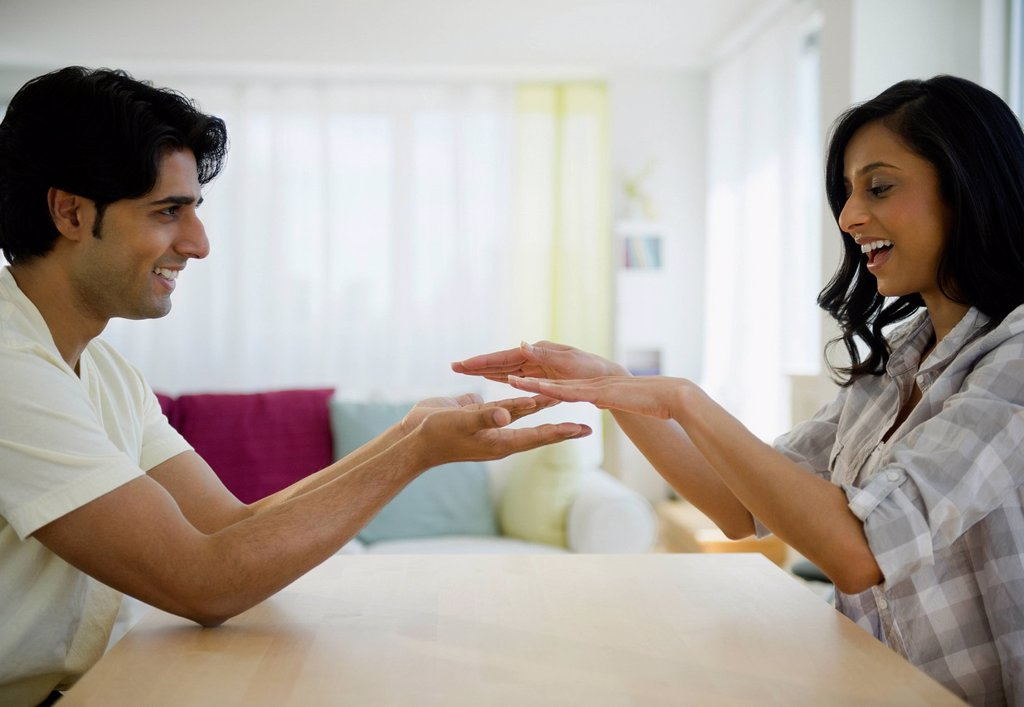 Stock Photo: 1589R-164644 Mixed race couple playing slapping game