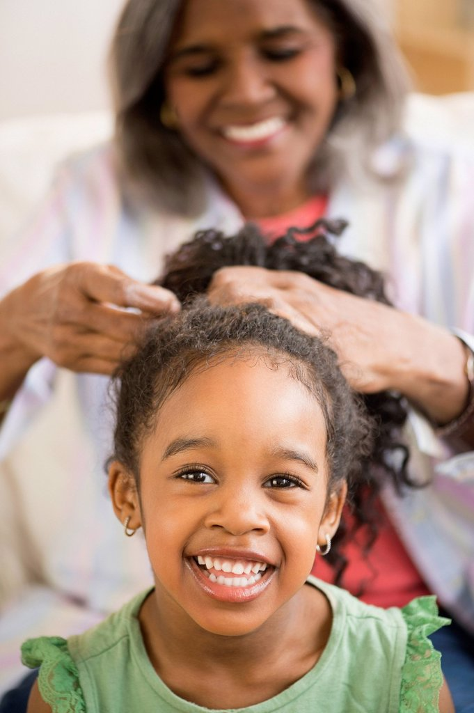 African American woman fixing granddaughter´s hair : Stock Photo