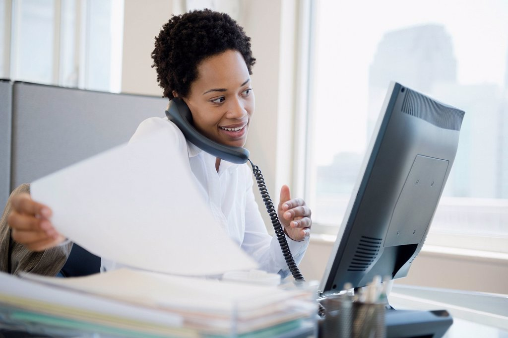 African American businesswoman using computer and talking on telephone : Stock Photo