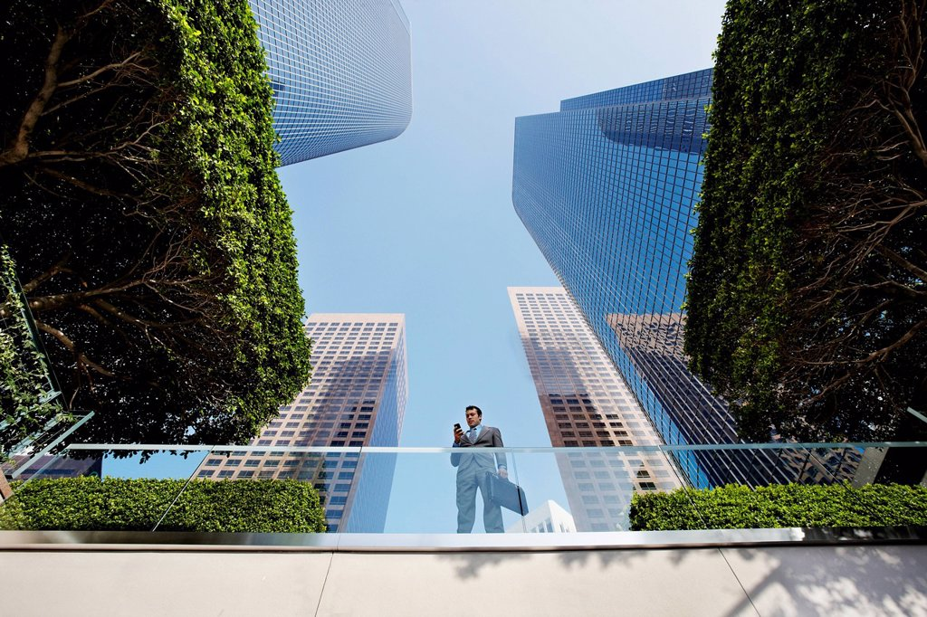 Businessman standing on balcony text messaging on cell phone : Stock Photo