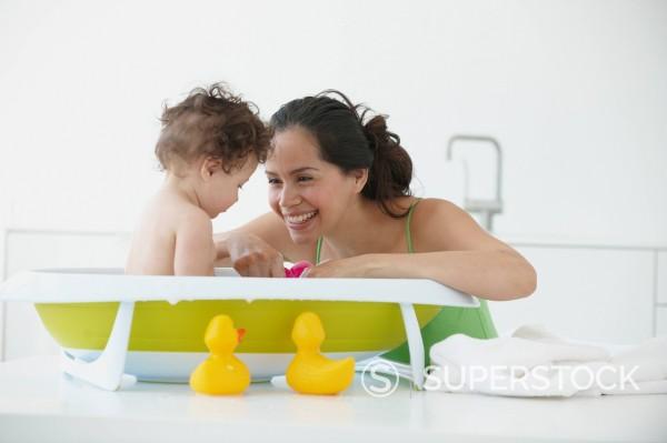 Hispanic woman giving daughter a bath : Stock Photo