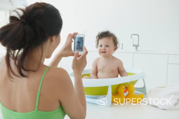 Hispanic woman taking photographs of daughter in bath : Stock Photo