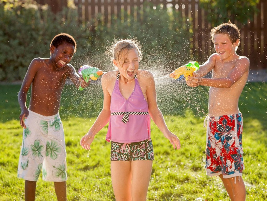 Stock Photo: 1589R-165489 Boys squirting girl with water guns