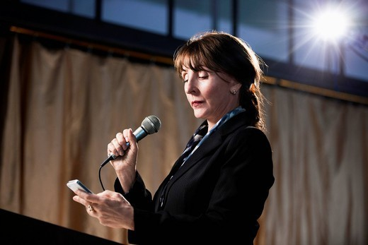 Stock Photo: 1589R-166290 Caucasian businesswoman speaking into microphone and using cell phone